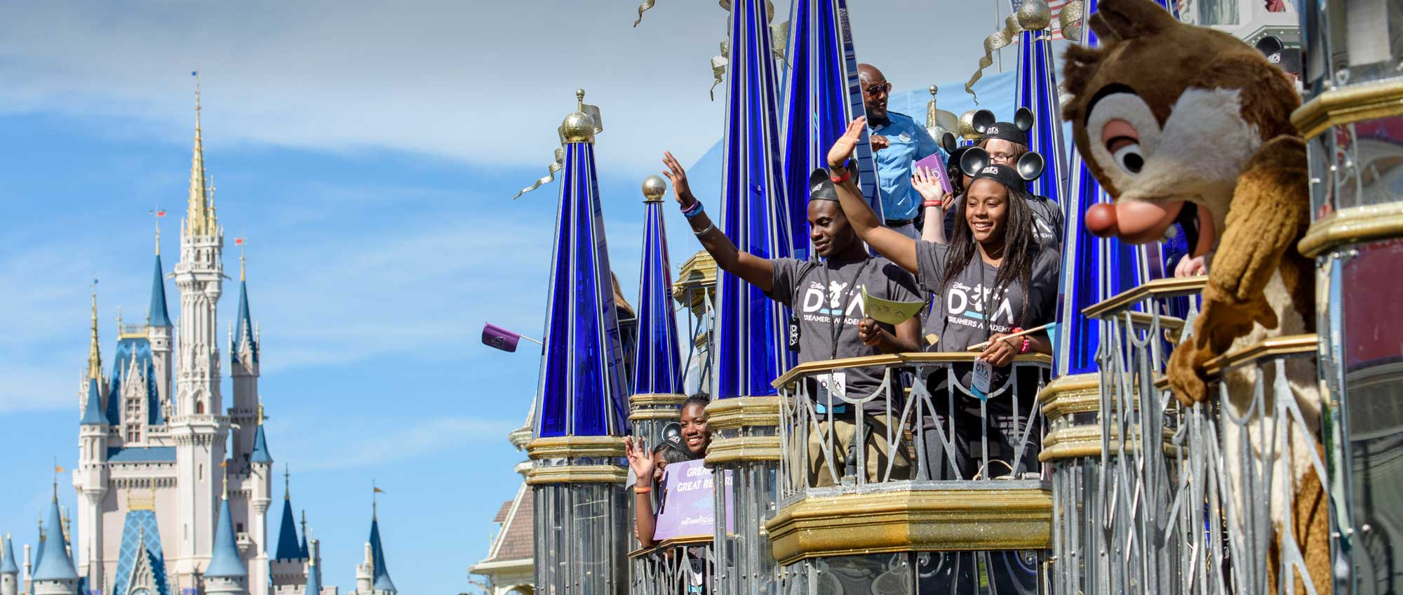 Teenage members of the Disney Dreamers Academy wave from a balcony at Magic Kingdom park as the Character Dale looks on