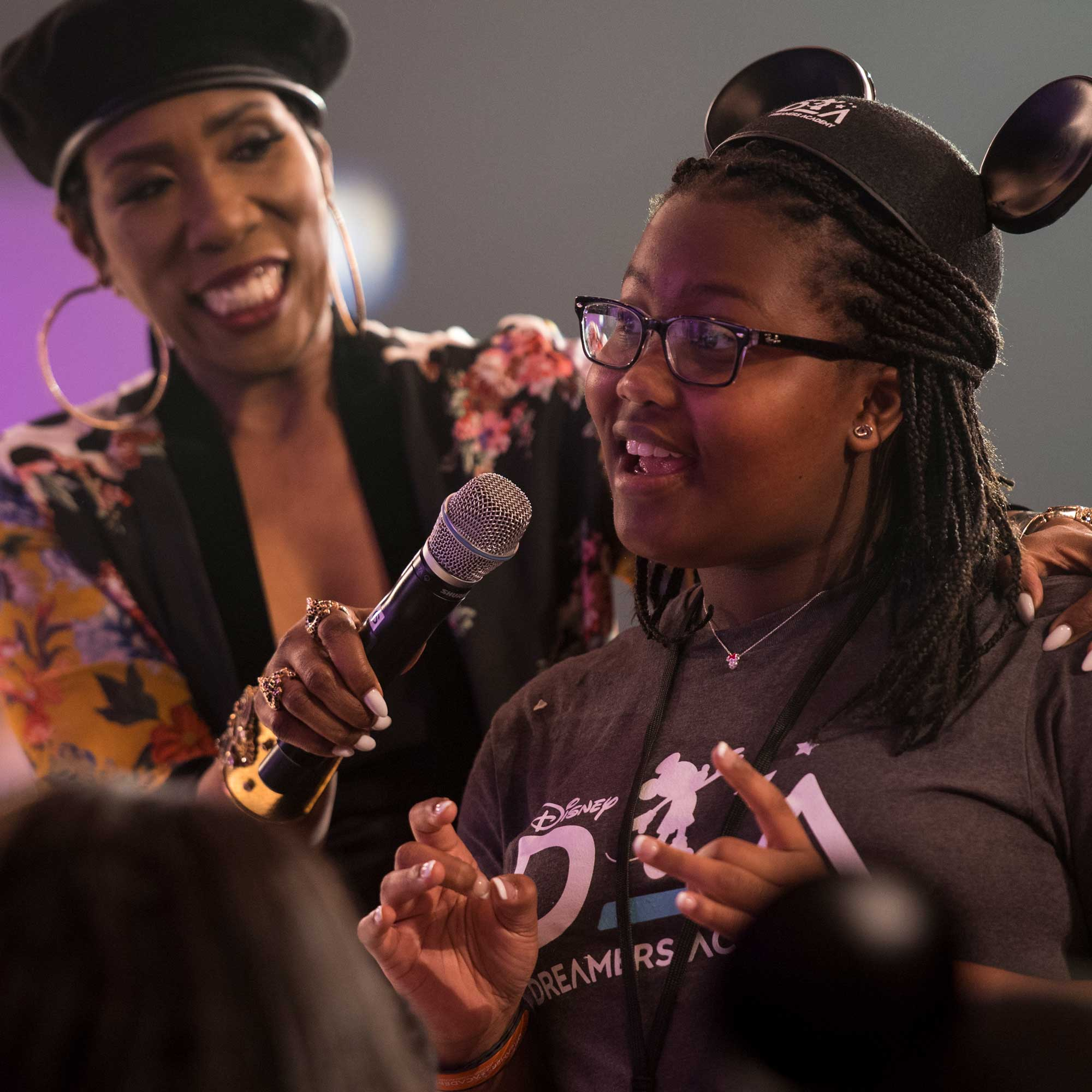 A woman holding a microphone as a teenage member of the Disney Dreamers Academy speaks