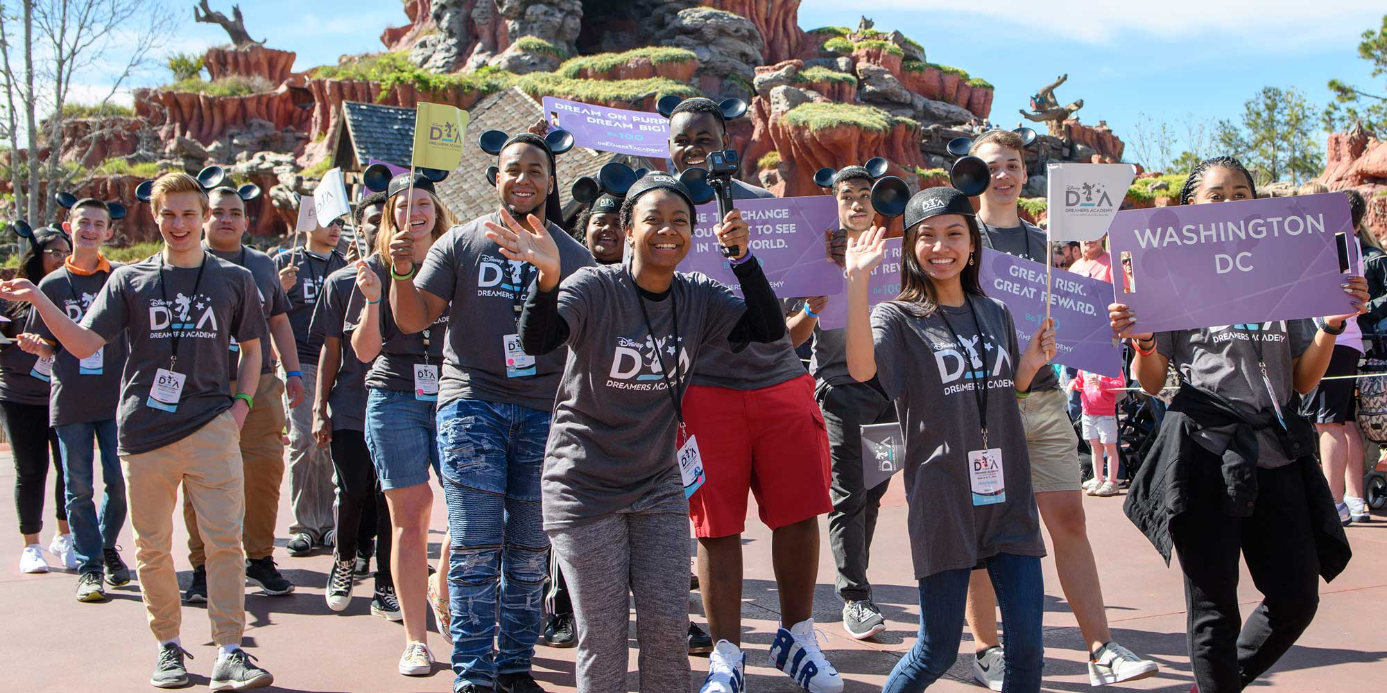 Teenage members of the Disney Dreamers Academy, wearing matching tee shirts and Mickey Mouse ears, hold small Academy flags and signs with inspiring messages