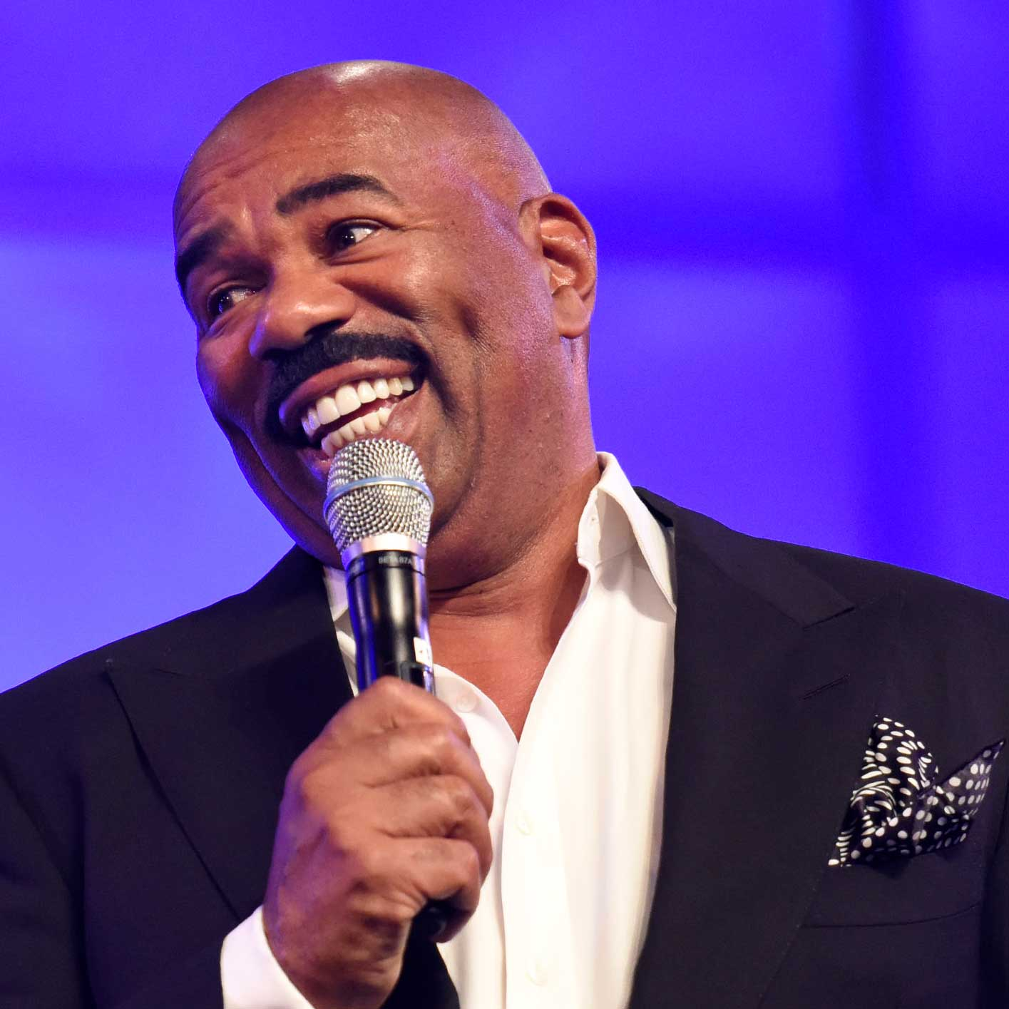 Entertainer Steve Harvey speaking into a microphone