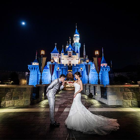 Groom kissing bride on the hand at Hong Kong Disneyland Castle