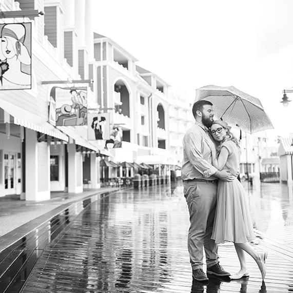 Bride and groom under umbrella during rain at the BoardWalk