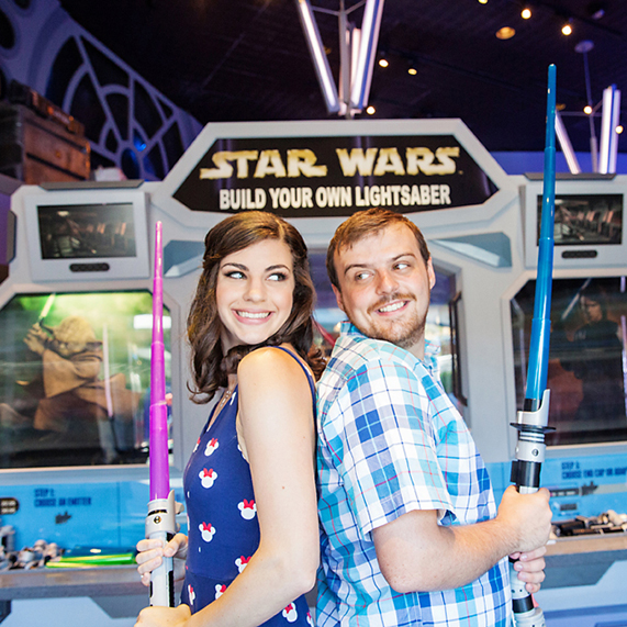 Star Wars engagement session with couple holding lightsabers.