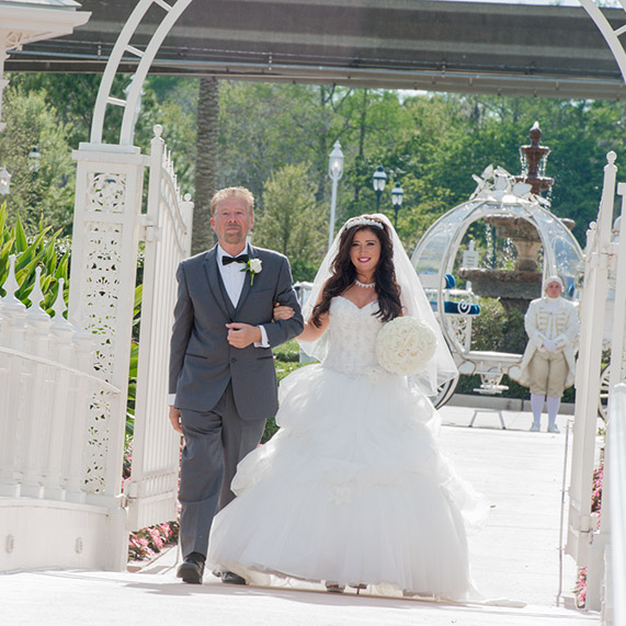 Bride and father walking across bridge to Disney's Wedding Pavilion