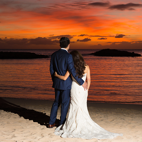 Bride and groom holding each other watching the sunset on the beach of Aulani