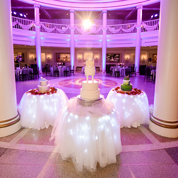 Three cakes on a glow table for purple lit reception at American Adventure Rotunda.