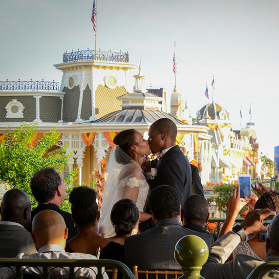 Bride and groom kissing at Magic Kingdom wedding ceremony.