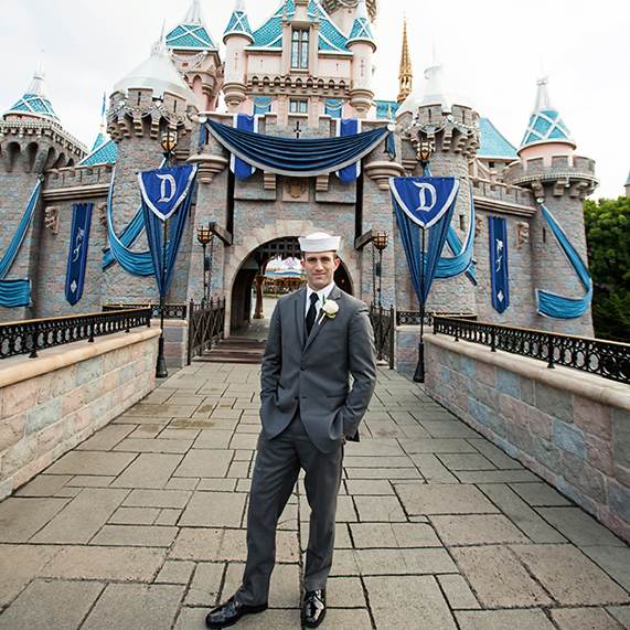 Groom wearing military hat and gray suit for Disneyland portrait session.