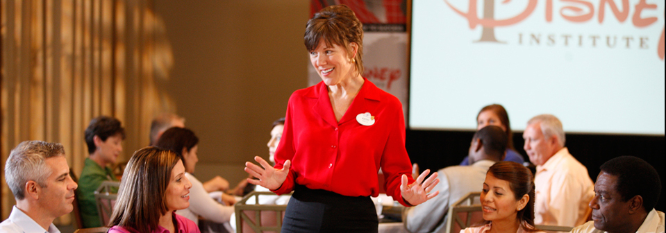 A woman wearing a name tag standing in front of a table of people