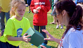 A woman delivers a box lunch to a girl on a sports field