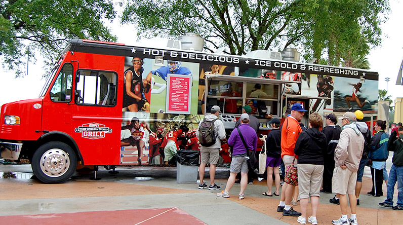 Guests line up at a food truck from the ESPN Wide World of Sports Grill