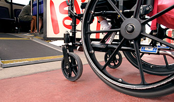 A wheelchair in front of a small ramp leading onto a Disney Transport bus