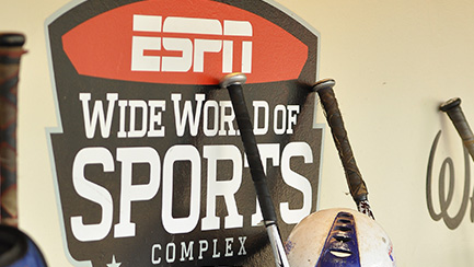 """Four baseball bats by a sign that reads """"ESPN Wide World of Sports Complex"""""""