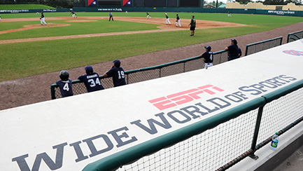 """Several baseball players on a field, by a banner that reads """"ESPN Wide World of Sports Complex"""""""