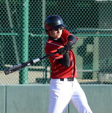 A teenage baseball player swings his bat