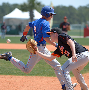 A baseball player attempts to beat a throw to the first baseman