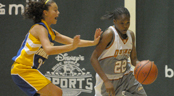 A teenage female basketball player dribbles with her left-hand around a defender
