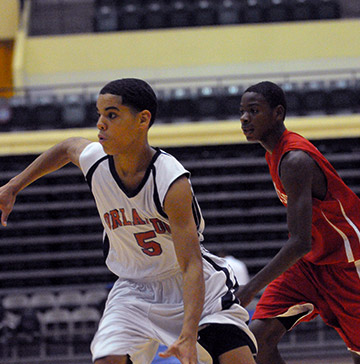 A teenage male basketball player dribbles past an opponent