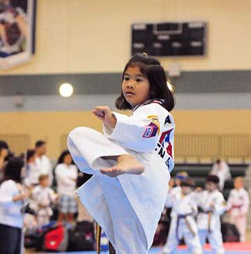 A girl in a gi performs a martial arts kick