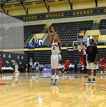 A basketball player takes a jump shot during warm-ups while a teammate looks on