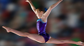 A young gymnast performing on a balance beam does the splits in mid-air