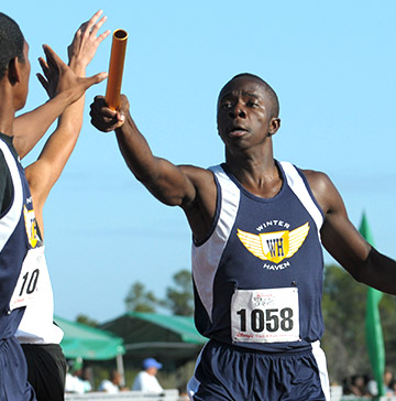 A long-distance relay runner hands a baton to his teammate