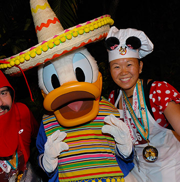 Donald wearing a serape and a sombrero poses with 2 runners at Disney Wine and Dine Half Marathon