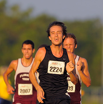 Three cross-country runners strain as they compete against each other