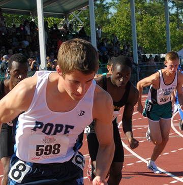 Runners competing on a track begin a long distance race