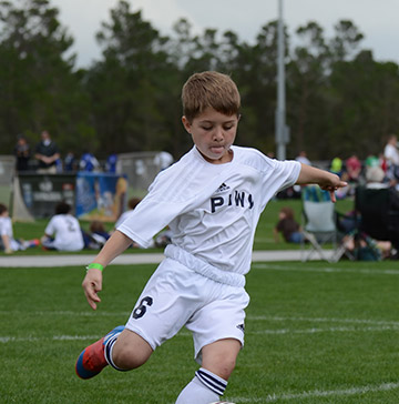 A little boy kicks a soccer ball
