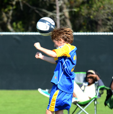 A young soccer player heads the ball while a spectator looks on
