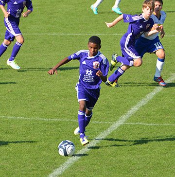 A boy sprints downfield with a soccer ball during a match and his teammates follow