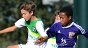 Opposing youth soccer players vie for control of a ball