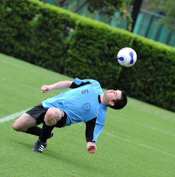 A soccer player nearly kneels to head a ball