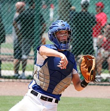 A baseball catcher follows through after tossing a ball