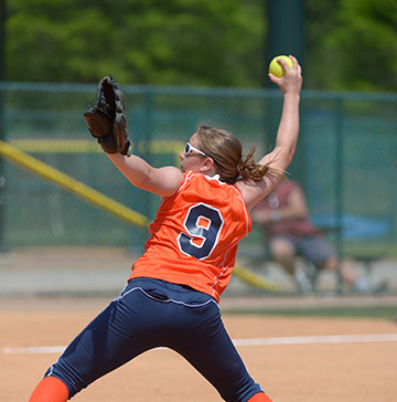 A softball pitcher stretches as she throws a softball