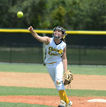 A softball player tosses a softball