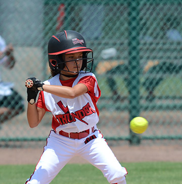 A young softball batter keeps her eye on a softball