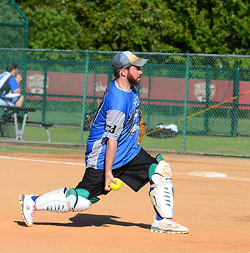 A pitcher wearing shin guards throws an underhand slow pitch