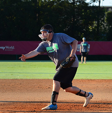 A pitcher wearing a face guard follows through on an underhand pitch
