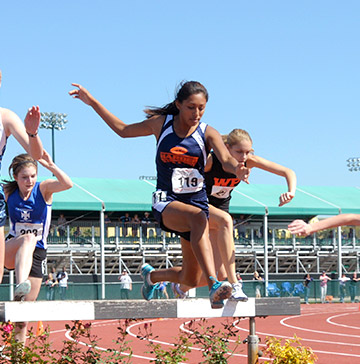 Three female steeplechasers negotiate a barrier to a water jump during a race
