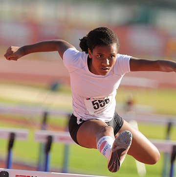 A female sprinter jumps a hurdle on a track