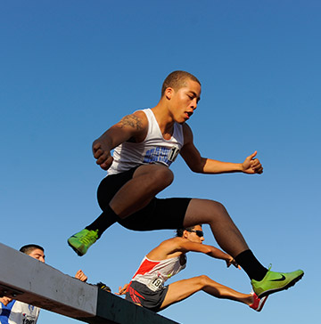 A steeplechase runner jumps over a wooden barrier before his competitors