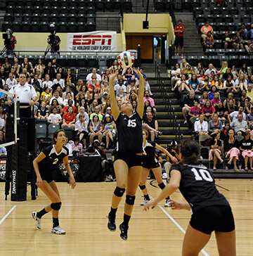 A volleyball player sets a ball for her teammate during a game