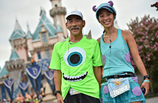 Mike Wazowski and Sulley runners in front of Sleeping Beauty Castle during Disneyland Half Marathon Weekend.