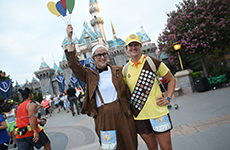 "Runners dressed as characters from ""Up"" pose in front of Sleeping Beauty Castle at Disneyland Park during Disneyland Half Marathon Weekend."