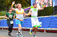 "Runners dressed as ""Toy Story"" characters run toward the finish line of Disneyland Half Marathon."