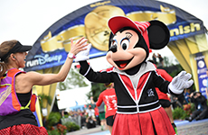 Runner high fives Minnie Mouse at the Walt Disney World Marathon finish line.