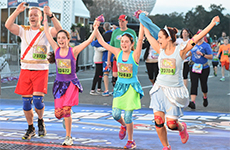 Family of runners crosses the finish line of the Walt Disney World 5K.