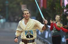 Runner dressed as Luke Skywalker crosses the finish line at Star Wars Half Marathon – The Light Side at Disneyland Resort.